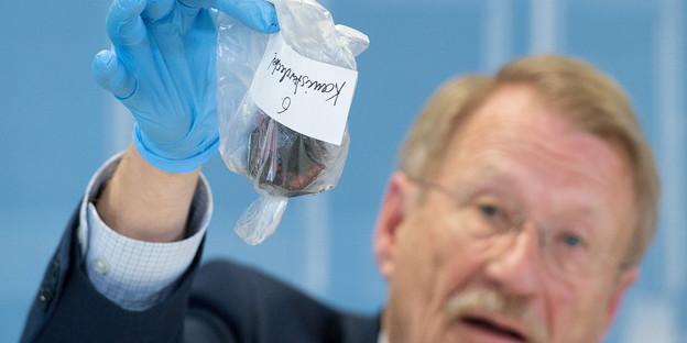 Wolfgang Drexler, der Vorsitzende des Landtags-Untersuchungsausschuss NSU in Baden-Württemberg, präsentiert am 18.03.2015 in Stuttgart (Baden-Württemberg) im Rahmen einer Pressekonferenz einen verkohlten Deckel eines Kanisters, den er von der Familie eines in einem Fahrzeug verbrannten Zeugen erhalten hat. Die Polizei hat angeblich die Beweismittel bei der ersten Untersuchung des Fahrzeugs nicht entdeckt. Foto: Bernd Weißbrod/dpa +++(c) dpa - Bildfunk+++