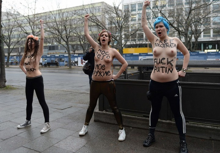 "Three topless Femen activists demonstrate in front of the Russian Embassy in Berlin on February 7, 2014. Femen staged the protest on the opening day of the Olympic Games in Sochi to demonstrate against Russian President Vladimir Putin's ""dictatorship and oppression of human rights in Russia"". AFP PHOTO / PATRIK STOLLARZ"